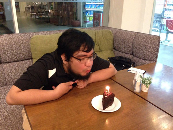 Birthday boy blowing candle on a slice of chocolate ganache